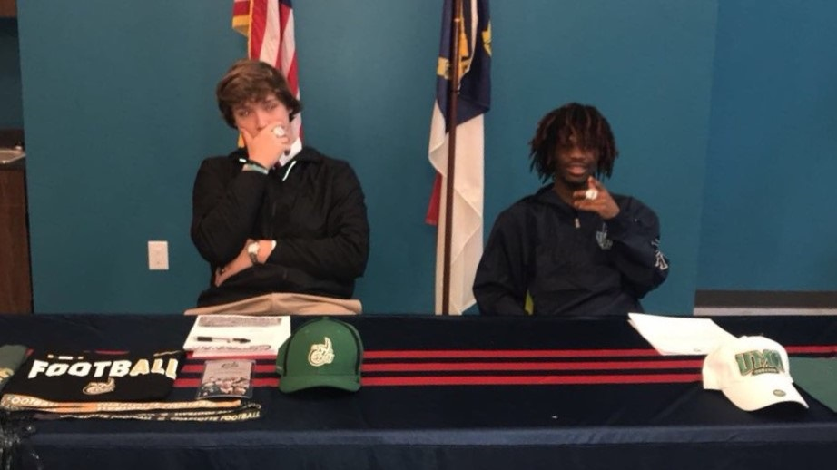 J is seen on the right, signing to play for the University of Mount Olive!