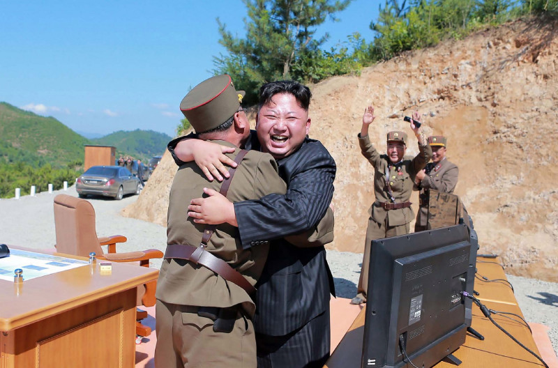 TOPSHOT - This picture taken on July 4, 2017 and released by North Korea's official Korean Central News Agency (KCNA) on July 5, 2017 shows North Korean leader Kim Jong-Un (C) celebrating the successful test-fire of the intercontinental ballistic missile Hwasong-14 at an undisclosed location. South Korea and the United States fired off missiles on July 5 simulating a precision strike against North Korea's leadership, in response to a landmark ICBM test described by Kim Jong-Un as a gift to
